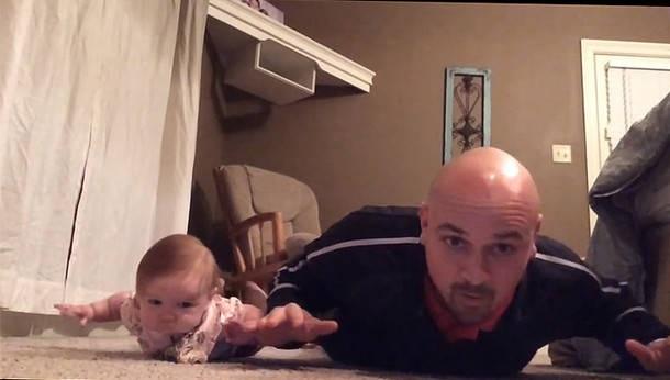 Un bebé de seis meses hace flexiones con su padre